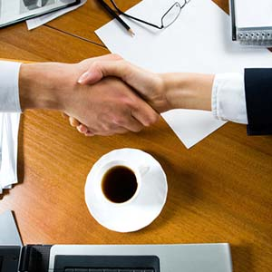 Close-up of people making a deal with a handshake over the table